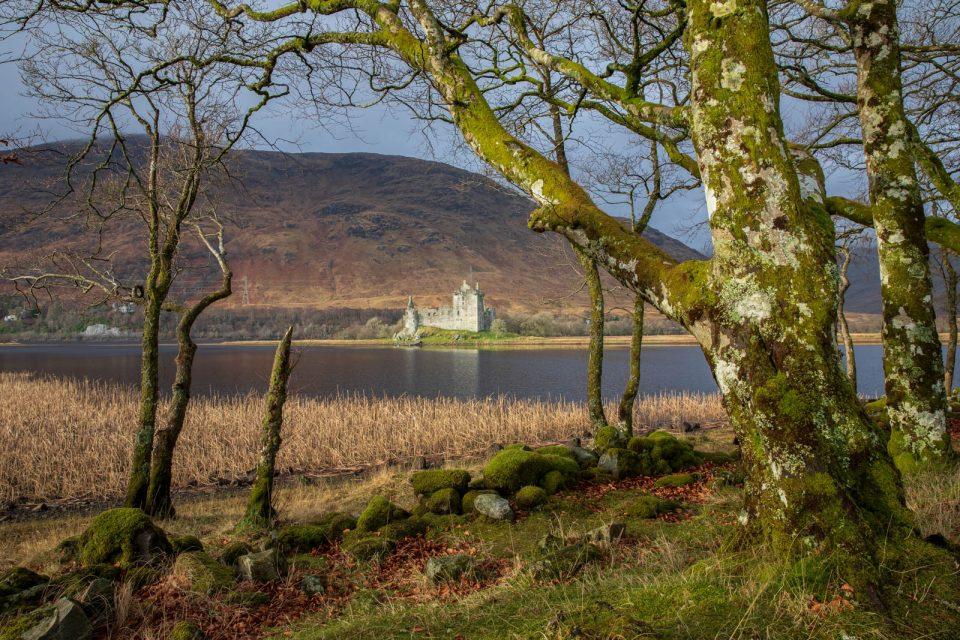 Schottland pur: Kilchurn Castle, bemooste Steinmauer und Bäume, ein Loch.